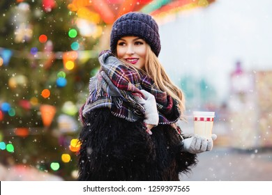 Outdoors lifestyle fashion portrait of pretty blonde girl walking on the holiday city in blizzard. Smiling, drinking coffee. Wearing stylish fur coat, hat and wide scarf. It's snowing. Christmas mood