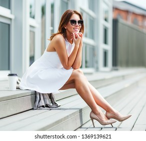 Outdoors lifestyle fashion portrait of pretty smiling red hair girl sitting on the bench. Enjoing the sun and resting. Trendsetter. Wearing stylish sunglasses, white dress, high heels. Happy woman