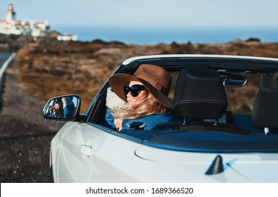 Outdoors lifestyle fashion portrait of pretty young woman driving cabriolet. Happy girl smiling, holding hat, looking at road. Wearing stylish jeans coat, hat, sunglass. Woman driving. Travel  by car