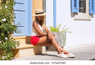 Outdoors lifestyle fashion portrait of pretty young woman sitting on stoop. Wearing stylish straw hat and red shorts. Travelling, walking on the summer city. Summer holiday. Relaxation