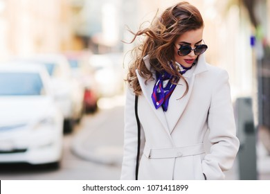 Outdoors lifestyle fashion portrait of stunning brunette girl. Walking on the city street. Going shopping. Wearing stylish white fitted coat, purple neckscarf, round rim sunglasses. WInd in the hair