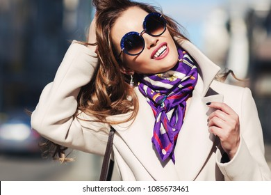 Outdoors lifestyle fashion portrait of stunning brunette girl. Smiling and walking on the city street. Going shopping. Wearing stylish white fitted coat, purple neckscarf, round rim sunglasses.