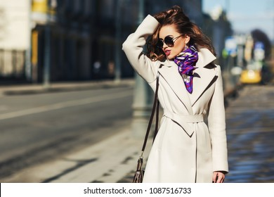 Outdoors lifestyle fashion portrait of stunning brunette girl. Walking on the city street. Going shopping. Wearing stylish white fitted coat, purple neckscarf, round rim sunglasses. Hand in the hair