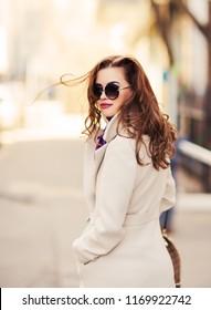 Outdoors lifestyle fashion portrait of stunning brunette girl. Walking on the city street. Going shopping. Wearing stylish white fitted coat, purple neckscarf, round rim sunglasses. Looking back
