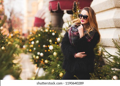 Outdoors lifestyle fashion portrait of stunning blonde girl. Smiling, walking on the Christmas city. Going shopping. Trendsetter. Wearing stylish black fur coat, scarf and sunglasses. Festive mood