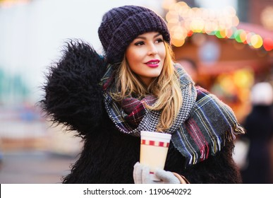 Outdoors lifestyle fashion portrait of stunning blonde girl walking on the holiday city. Smiling, drinking coffee and enjoying life. Wearing stylish fur coat, knitted hat and wide scarf. Festive mood