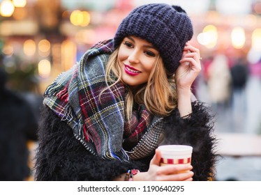 Outdoors lifestyle fashion portrait of stunning blonde young woman. Smiling, drinking hot mulled wine. Wearing stylish fur coat, knitted hat and wide scarf. Romantic mood. Festive background.