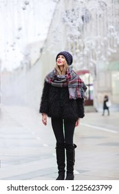 Outdoors lifestyle fashion portrait of stunning blonde girl. Smiling, walking on the festive city street. Holiday mood. Wearing stylish black fur coat, knitted hat and wide scarf. It's snowing.