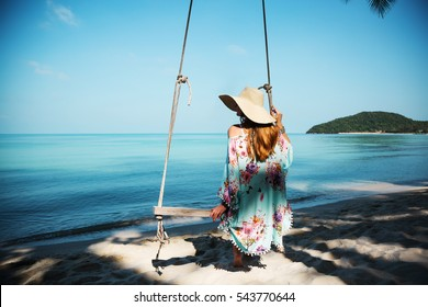 Outdoors lifestyle fashion portrait stunning girl sitting back on swing on the beach. Sea background. Wearing stylish blue dress, bracelets and straw hat. Straight long hair. Enjoying life in paradise