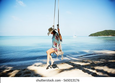 Outdoors lifestyle fashion portrait stunning girl sitting on swing on the beach. Sea background. Wearing stylish blue dress, bracelets and straw hat. Straight long hair. Enjoying life in paradise
