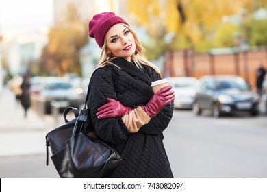 Outdoors lifestyle fashion portrait of stunning blonde girl. Smiling, drinking coffee and walking on the city street. Going shopping. Trendsetter. Wearing stylish black oversized coat and burgundy hat