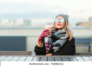 Outdoors lifestyle fashion portrait of stunning blonde girl. Sitting in an outdoor cafe on the roof. Drinking coffee and enjoying life. Wearing stylish black oversized coat, scarf, sunglasses and hat