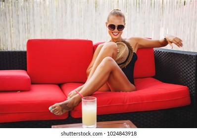 Outdoors lifestyle fashion portrait of young stunning happy woman. Laughing and enjoying life on the sunbed on the beach. Wearing stylish round sunglasses, straw hat and black bikini. Sunbathing.