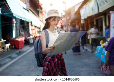 Outdoors lifestyle of happy young woman.  traveler young woman standing on holiday festival outdoor market famous local street market with backpack and looking map , tourism shopping street food