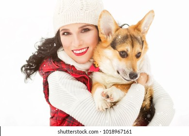 Outdoors lifestyle image of pretty girl hugging puppy corgi in the park. Beauty face. Wearing stylish knitted hat, sweater, vest. Playing with the dog. Close-up. Animal love concept. White background