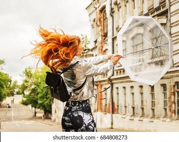 Outdoors lifestyle portrait of ginger hair girl in waterproof silver raincoat walking at downtown. Whirling with an umbrella. Opening transparent umbrella. Rainy weather season concept. Hurricane