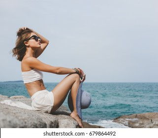 Outdoors lifestyle portrait of a girl dressed in a white dress with a hat in her hand sitting on the background of the sea