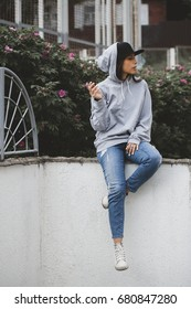 Outdoors lifestyle portrait os young woman sitting on the ground in the square, smoking a cigarette . Hoodie, cap, jeans, snickers swag girl concept