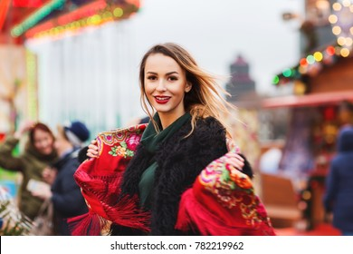 Outdoors lifestyle portrait of pretty blonde young woman. Smiling and walking on the holiday market. Wearing stylish black fur coat, shawl with a floral pattern in the Russian style. Festive mood