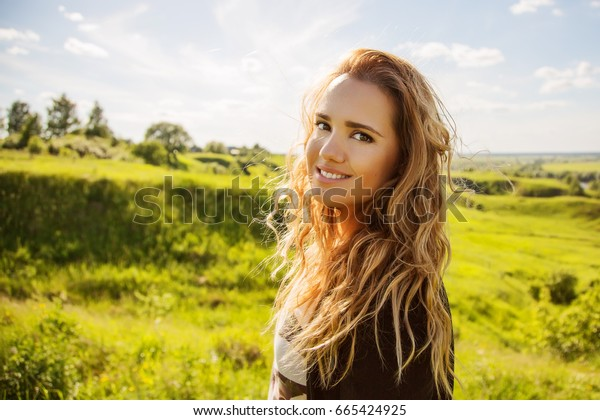 Outdoors lifestyle portrait of pretty blonde woman with long curly hair. Smiling and enjoying life on the nature weekend. Walking of the natural park. Freedom and happiness concept.