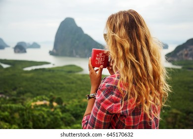 Outdoors lifestyle portrait of travelling girl holding a cup of coffee. Enjoying amazing view on the bay. Wearing checkered shirt. Early morning. Travelling and tourism concept.  Feeling freedom