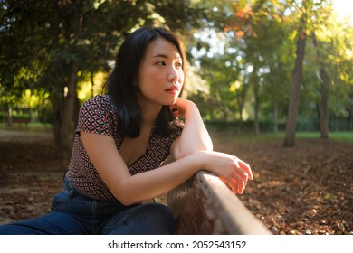 outdoors lifestyle portrait of young happy and beautiful Asian Korean woman relaxed and thoughtful at sitting pensive on city park bench in Autumn on a dreamy feeling