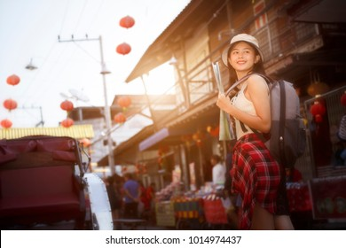 Outdoors lifestyle.  smiley beautiful woman standing in front of festival outdoor market famous with backpack , tourism shopping  Festive mood, Traveler , holidays, Backpacker concept, blur background