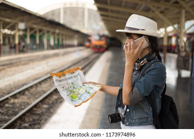 Outdoors lifestyle of young woman. talking on the mobile phone while is waiting in a train station for enquiring about travel destinations,Travel and holidays, Backpacker concept.