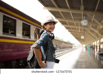 Outdoors lifestyle of young woman. tourist girl walking at the railway station and turning back and sincere smile,  Travel and holidays, Backpacker concept.