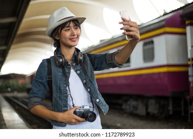 Outdoors lifestyle of young woman. tourist girl joyful cheerful taking a selfie while walking at the railway station and sincere smile,  Travel and holidays, Backpacker concept.