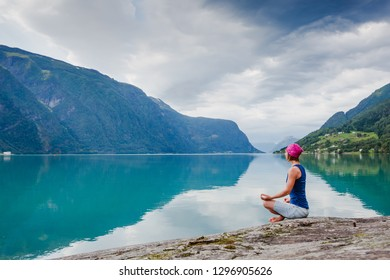 outdoors meditation - relaxed young yoga woman in yoga pose near the lake