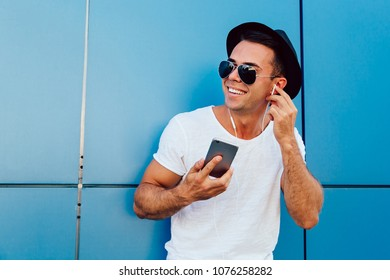 Outdoors photo of attractive guy in sunglasses listening to music in earphones on his smartphone, enjoying the song. Dressed in white t-shirt and black hat. Outdoors.