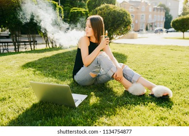 Outdoors photo of trendy attractive girl smoking vape, spending leisure time while sitting on grass in the park, with laptop.