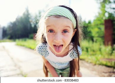 Outdoors portrait of amazed child girl with protruding tongue
