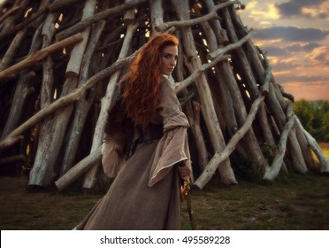 Outdoors portrait of beautiful furious scandinavian warrior ginger woman in a traditional clothes with fur collar, with sword in her hand and wooden Nikola-Lenivets view on the background.