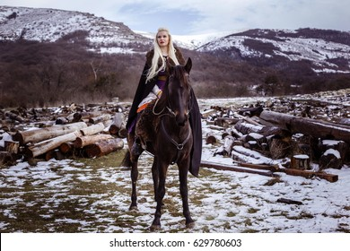 Outdoors portrait of beautiful furious scandinavian warrior ginger woman in a traditional clothes with fur collar, with sword in her hand and wooden Viking Village view on the background.