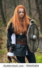Outdoors portrait of beautiful furious scandinavian warrior woman with with sword, shield and red hair in a traditional clothes with fur collar, war makeup, with forest background