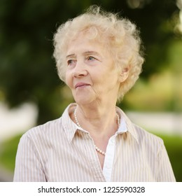 Outdoors portrait of beautiful smiling senior woman with curly white hair. Elderly lady walking in summer park. Active longevity concepts