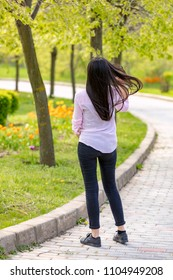 Outdoors portrait of beautiful teenager brunette girl walking in park