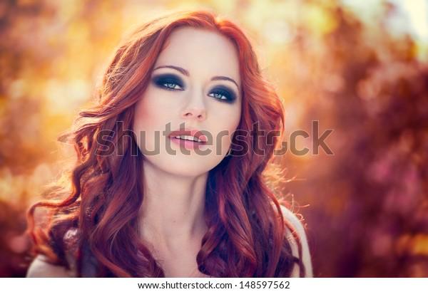 Na zewnątrz portret pięknej kobiety z rudymi włosami i zadymionymi oczami makijaż