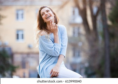 Outdoors portrait of beautiful young girl laughing