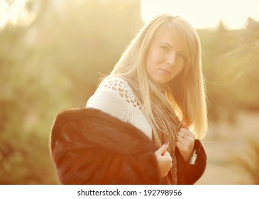 Outdoors portrait of a girl with long blond hair in a black fur coat