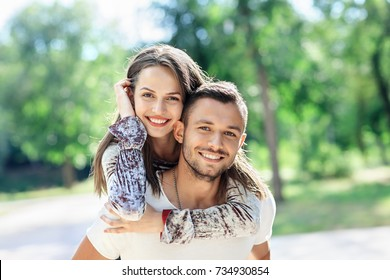 Outdoors portrait of lovers happy young man and woman looking at camera. Smiling girl piggyback of her boyfriend. Love, youth, relationship concept photo on nature background on sunny day