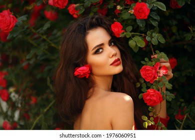 Outdoors portrait of Natural Beautiful woman in red roses. Sensual female with rose flowers in hair. Sexy brunette with makeup over sunset blossom park. Passion and expression. Spanish flamenco style.