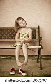 Outdoors portrait of small cute child with hanging legs - sepia tone