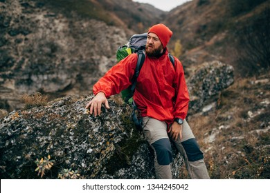 Outdoors portrait of tired hiker man in red clothes sitting on the rock relaxing after hiking in mountain. Traveler male have a break after trekking during journey. Travel, people, sport, lifestyle