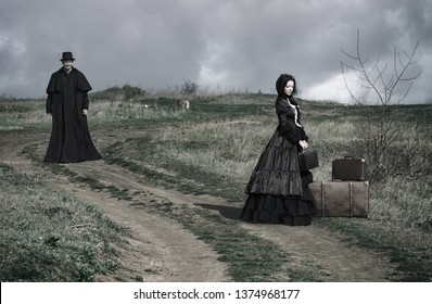 Outdoors portrait of a victorian lady in black sitting on the road with her luggage and gentleman walking down the road.
