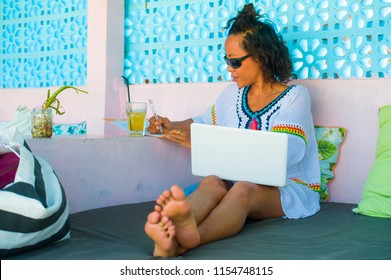 outdoors portrait of young attractive and happy hipster looking woman working online with laptop computer at cool coffee shop in successful entrepreneur and digital nomad lifestyle