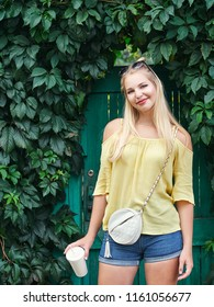 Outdoors portrait of young beautiful blonde woman with high bun hairstyle jeans shorts yellow blouse enjoying journey weekend posing against vintage green wooden fence with ivy
