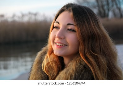 Outdoors portrait of young beautiful smiling girl with red cheeks in winter near the frozen lake at sunrise